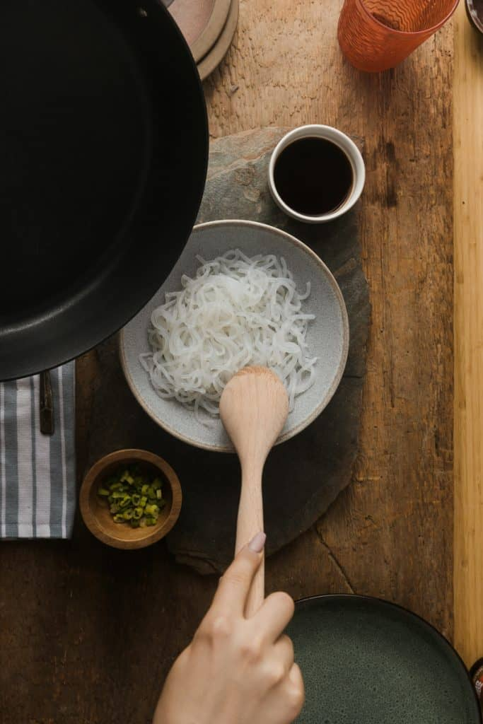 Stirring miracle noodles in a bowl with a wooden spoon