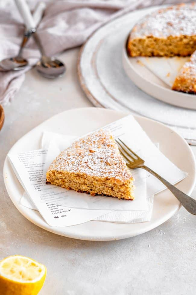 A single piece of Almond Cake on a white plate with a fork. Lemon and the rest of the cake surround it.