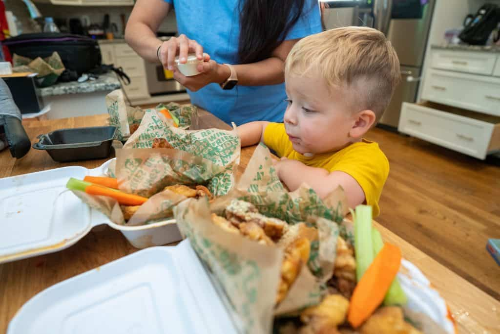 woman and her toddler eating chicken wings from takeout boxes
