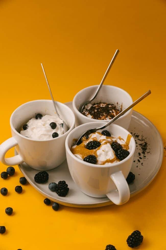 three flavors of keto mug cakes on a plate in coffee mugs