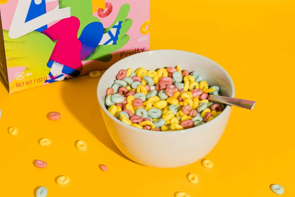 bowl of mutli colored cereal on orange background with a spoon
