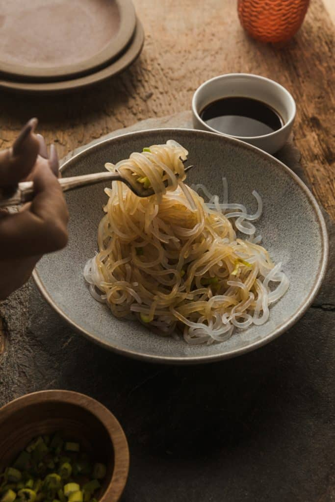 Miracle noodles in a bowl with soy sauce on them and off to the side.  A fork dipped in pulling noodles out.