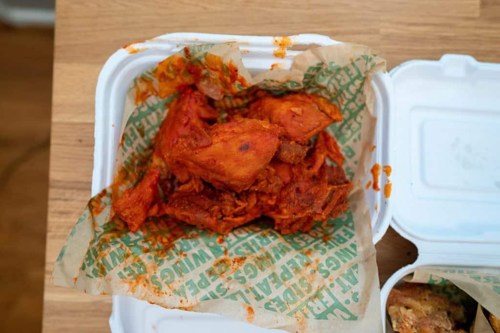 original hot wings in a cardboard takeout box