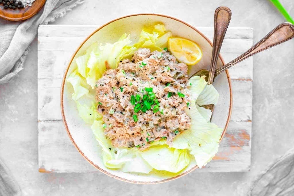 Tuna salad in a bowl over top lettuce leaves and spoon sticking out.