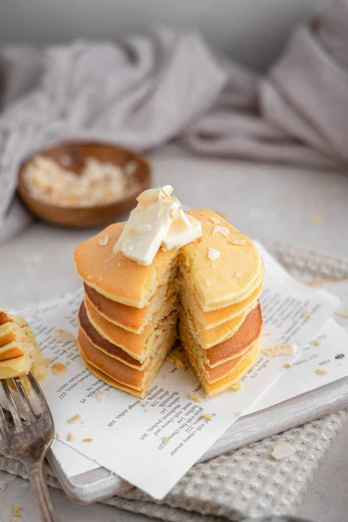 Sliced protein pancakes with a pat of butter and flecks of coconut