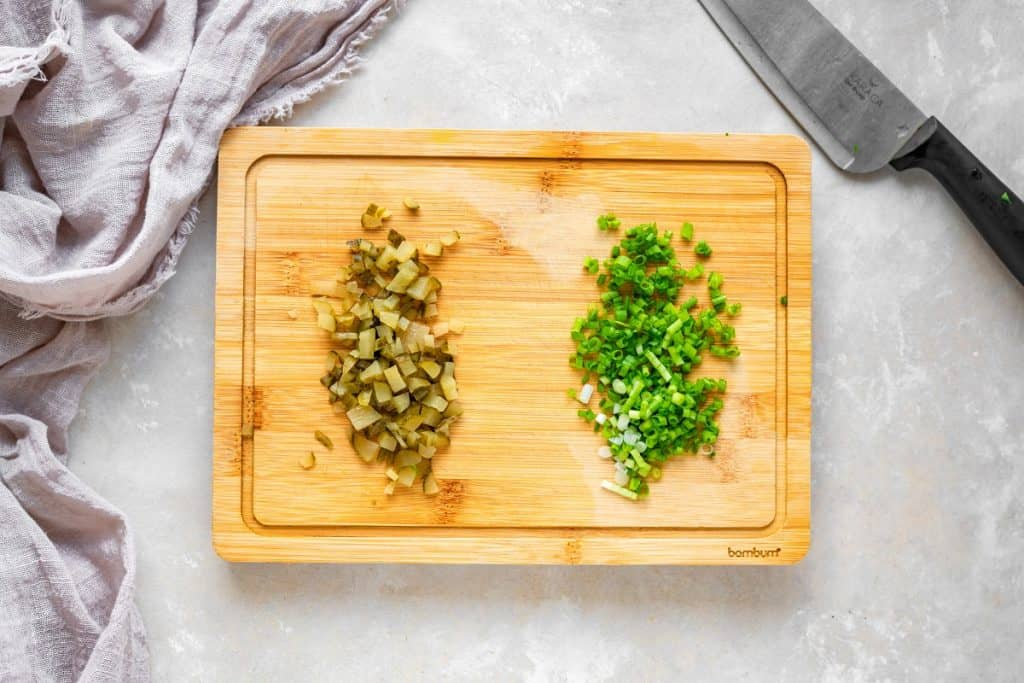 Overhead shot of pickle and green onion laid out on a cutting board with a knife beside it.