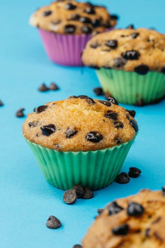 keto chocolate chip muffins on a blue table in muffin liners
