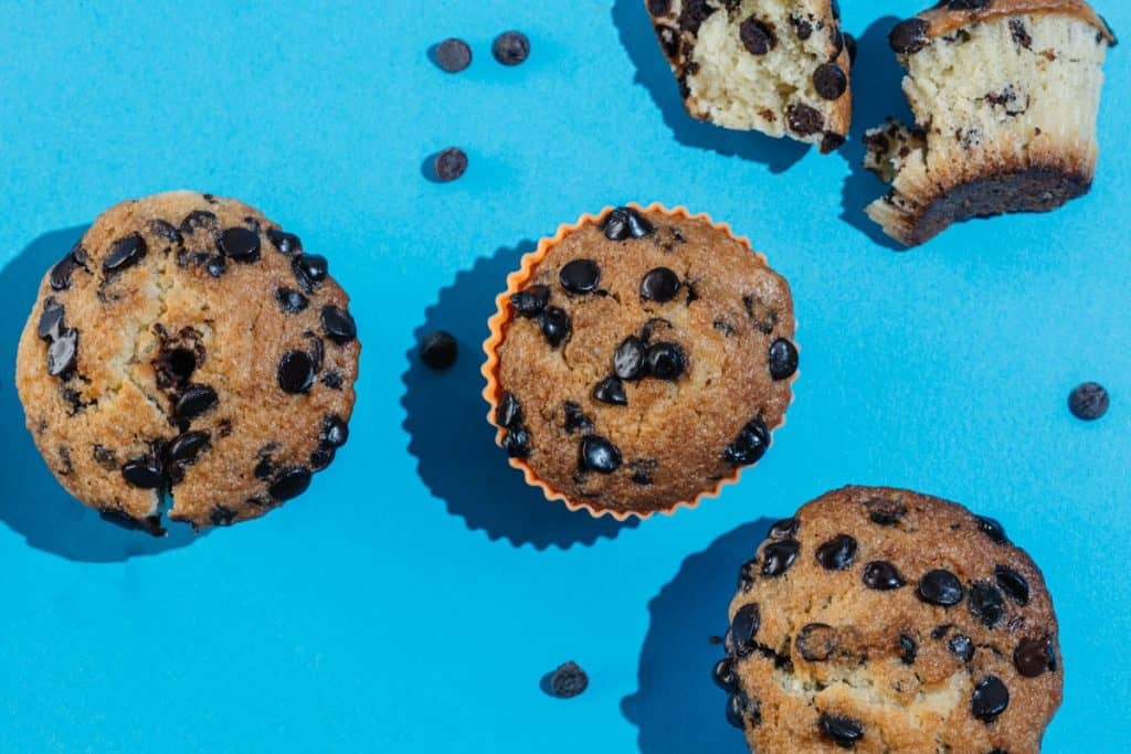 Bright blue backdropped chocolate chip muffin pop art.