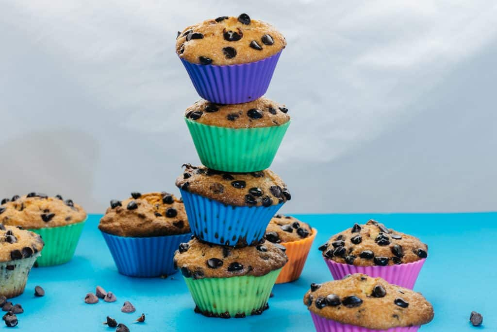 Four keto muffins stacked in a tower surrounded by other muffins.