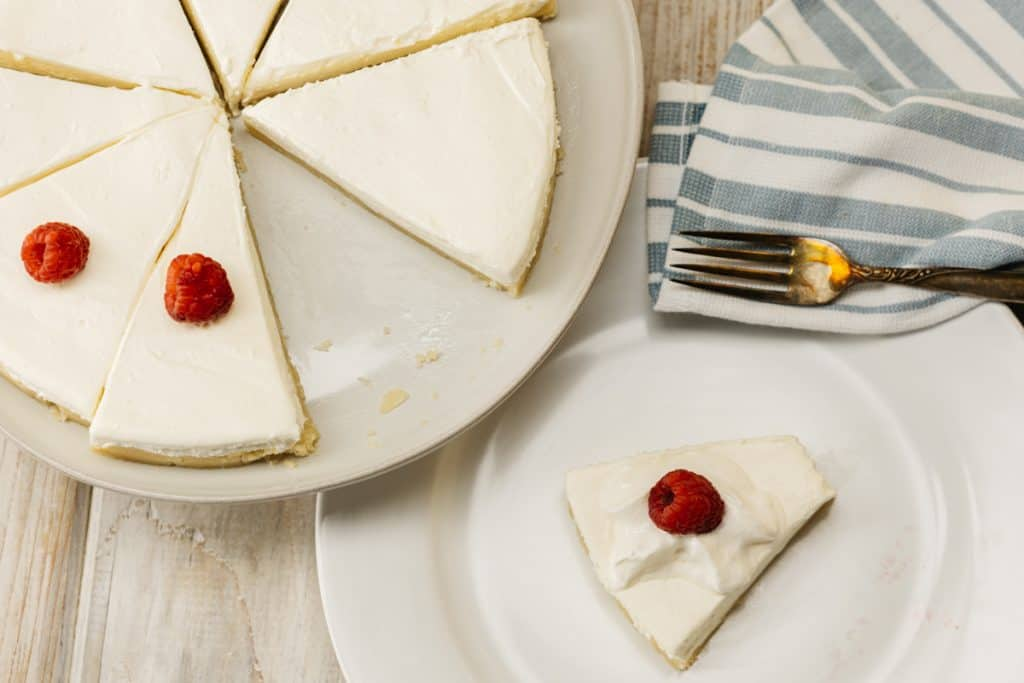 Overhead shot of Keto No bake cheesecake on a platter with one slice on a plate to the side