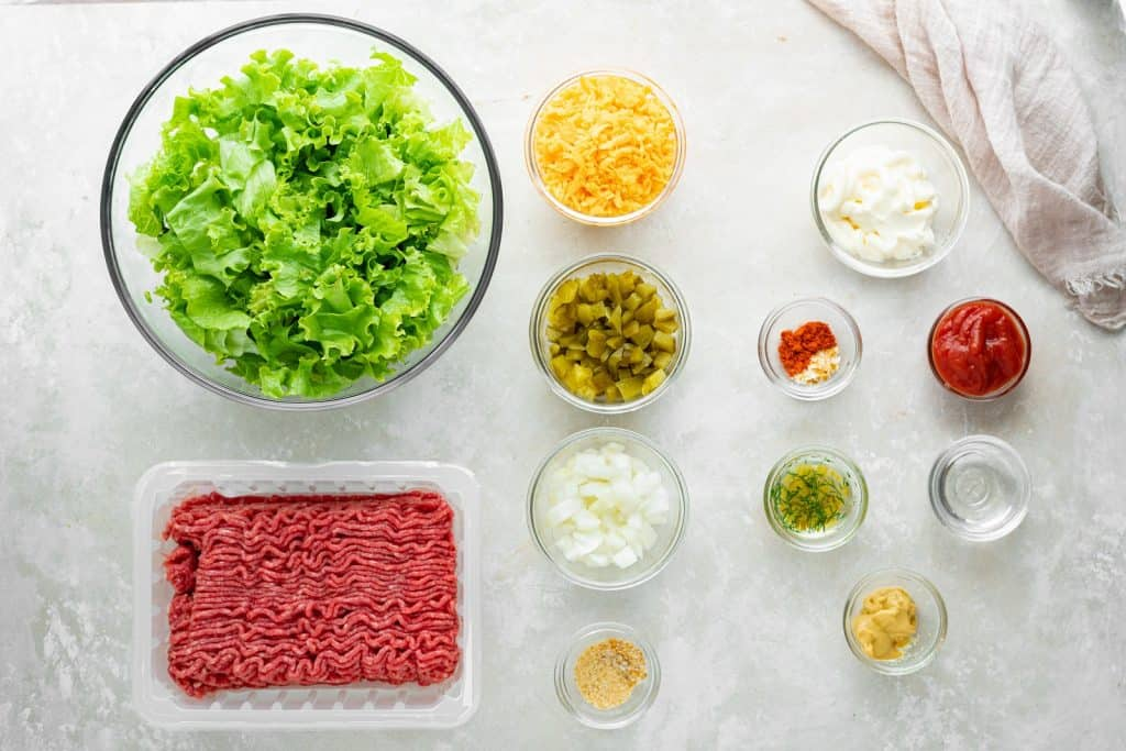 All the ingredients for a big mac salad in separate bowls