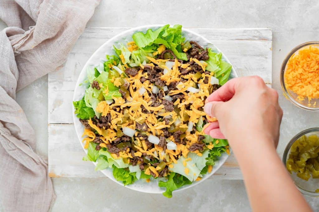 Sprinkling cheese on a Big Mac salad. Salad is in a white bowl sitting on a rustic white washed board.