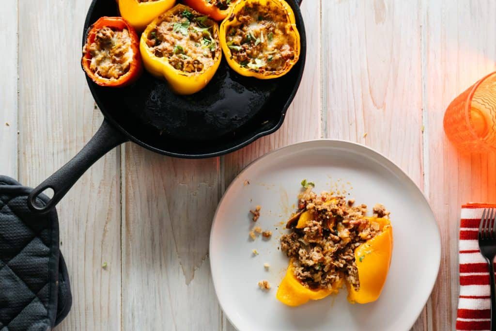A plate with one keto stuffed pepper on it and several in a pan next to the plate