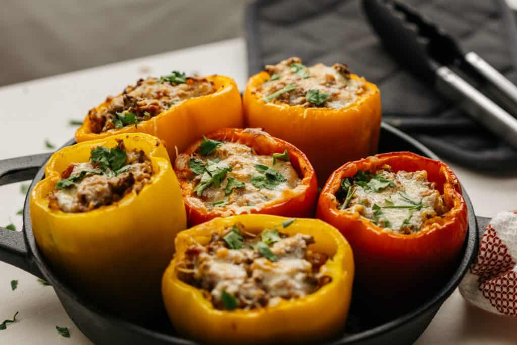 A variety of stuffed bell peppers filling a cast iron pan