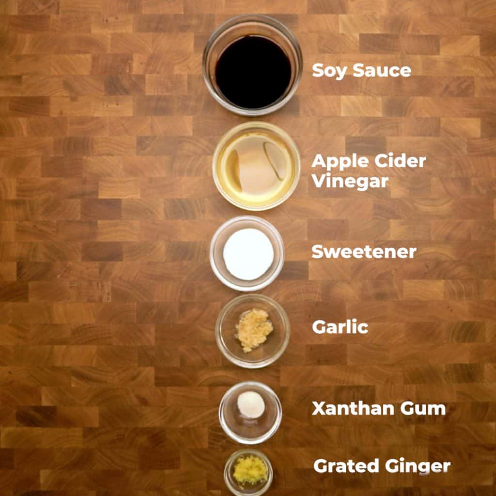 Overhead shot of ingredients for keto teriyaki sauce in bowls on a table. they are all labeled
