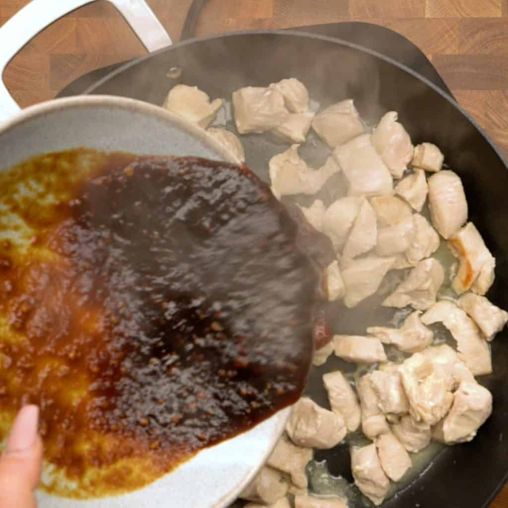 Overhead shot of keto teriyaki saucing being poured onto cooking chicken in a frying pan.