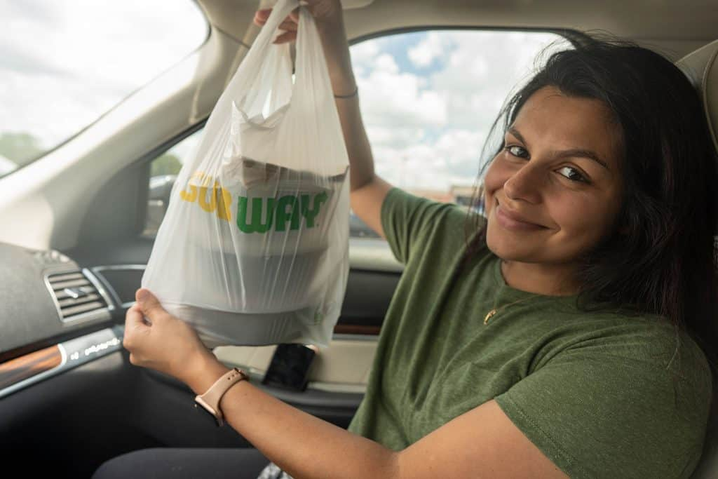 Megha holding up a bag of subway food in a car