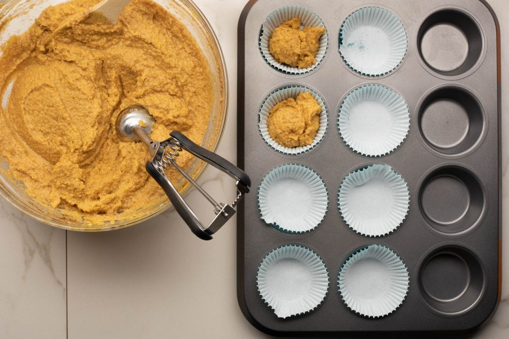using a cookie scooper to put the muffin batter in the baking tins