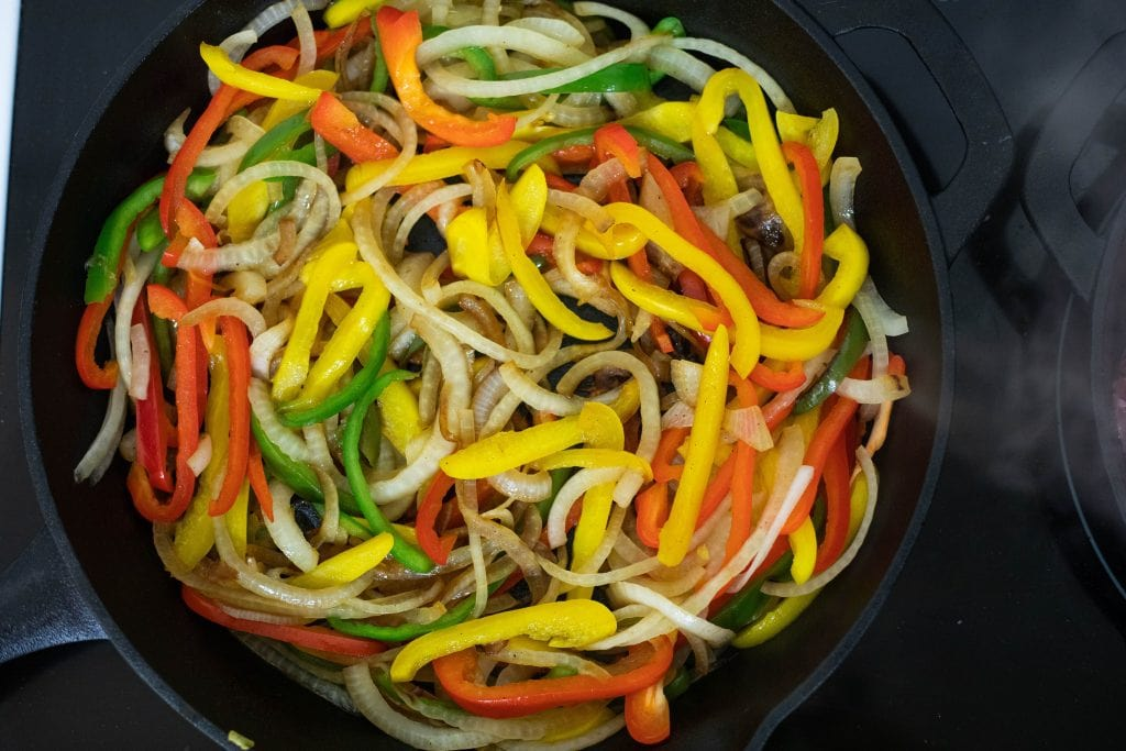 cooking down peppers and onions for a tender fajita base