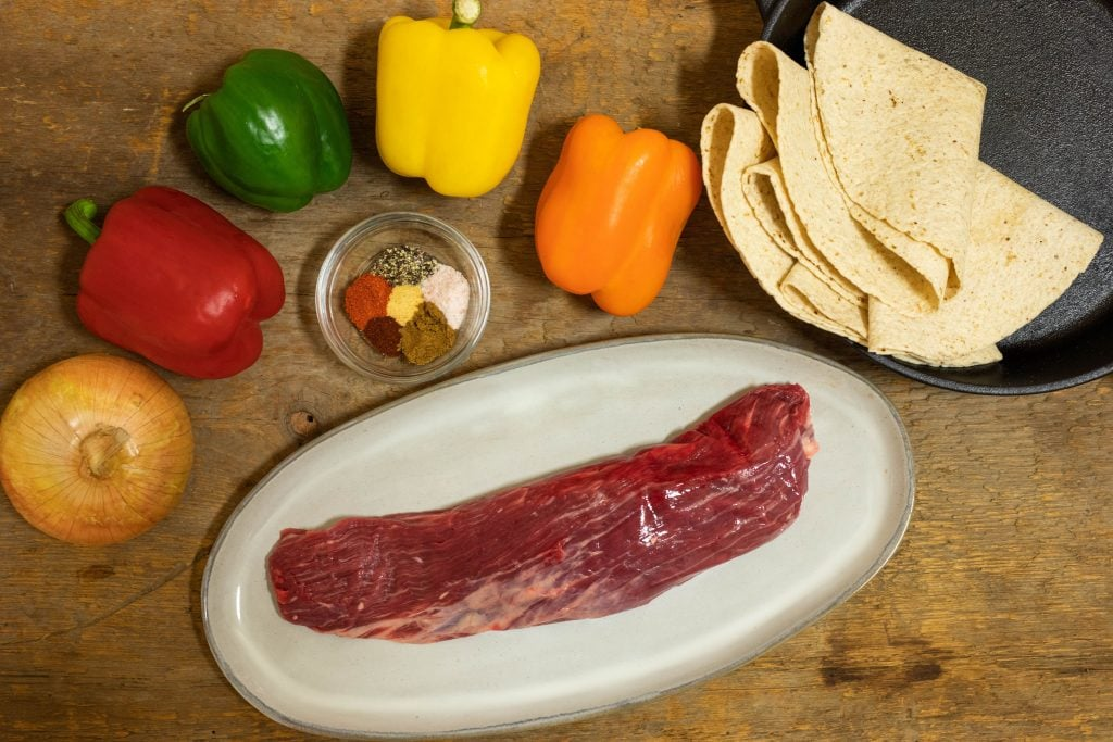 All the ingredients to make keto fajitas placed on an aged wooden table