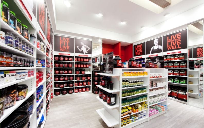 lighted gnc store with shelves of supplements