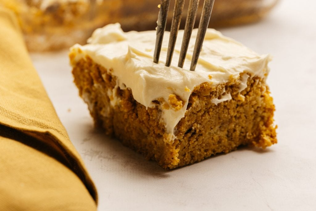 close up of a single pumpkin bar with cream cheese frosting