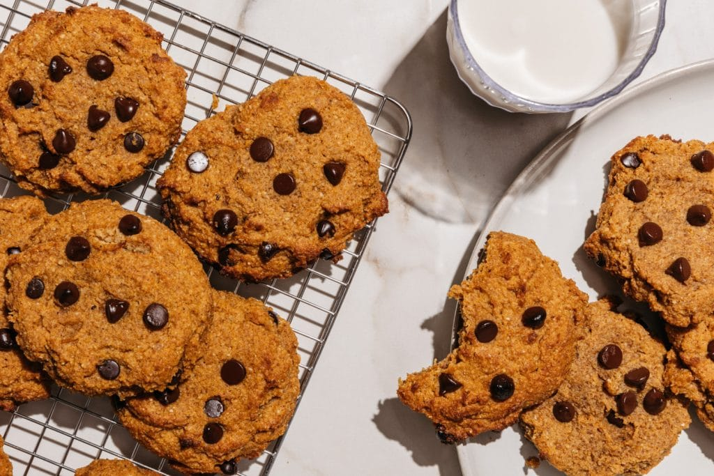 keto pumpkin chocolate chip cookies on a cooling rack with a glass of milk