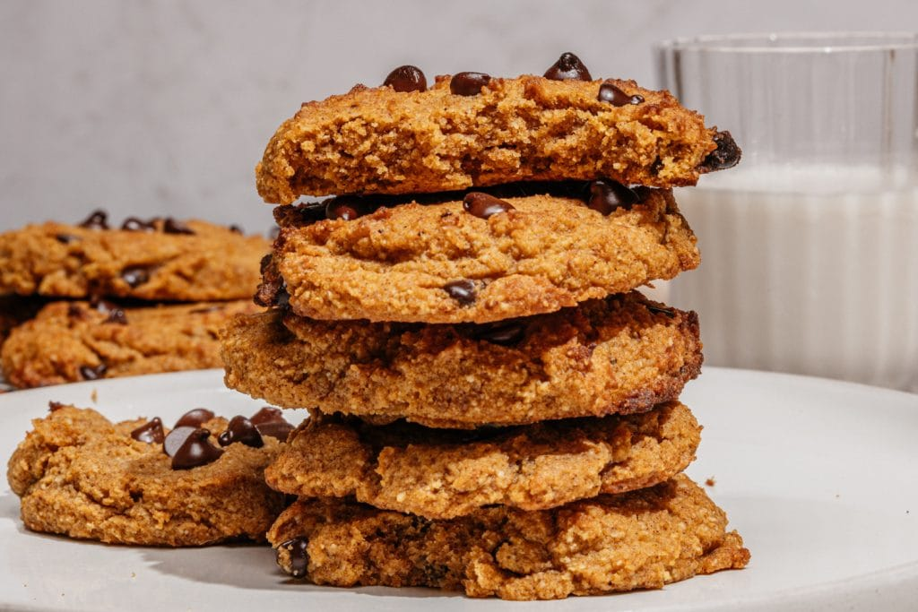cookies stacked on the table with a glass of milk in the background