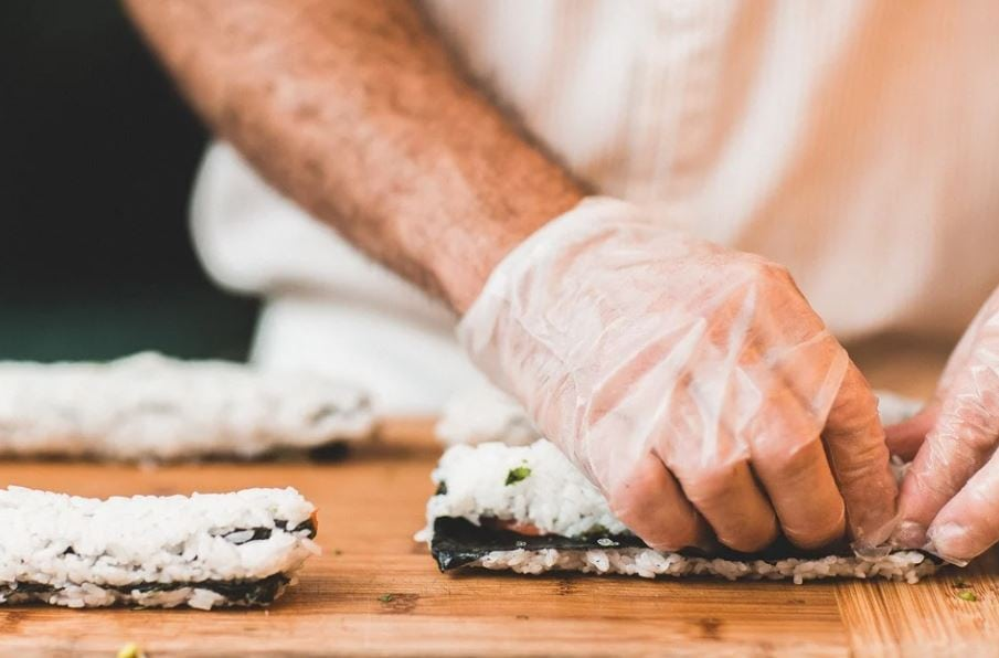 chef making a sushi roll with rice