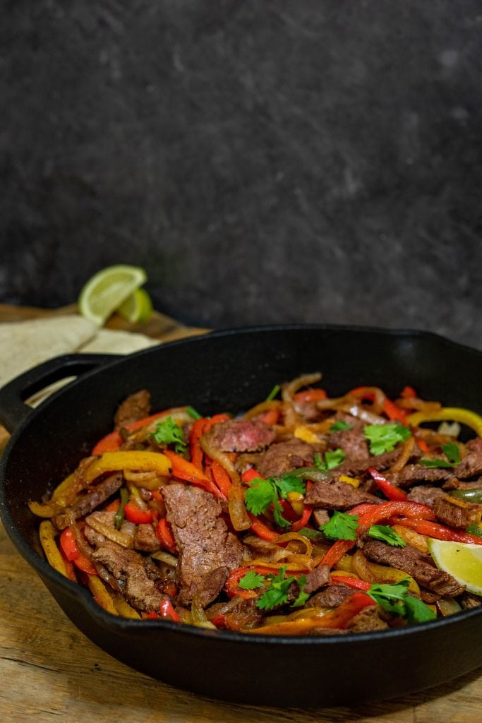 A cast iron skillet placed on the table full of sautéed steak and vegetables.