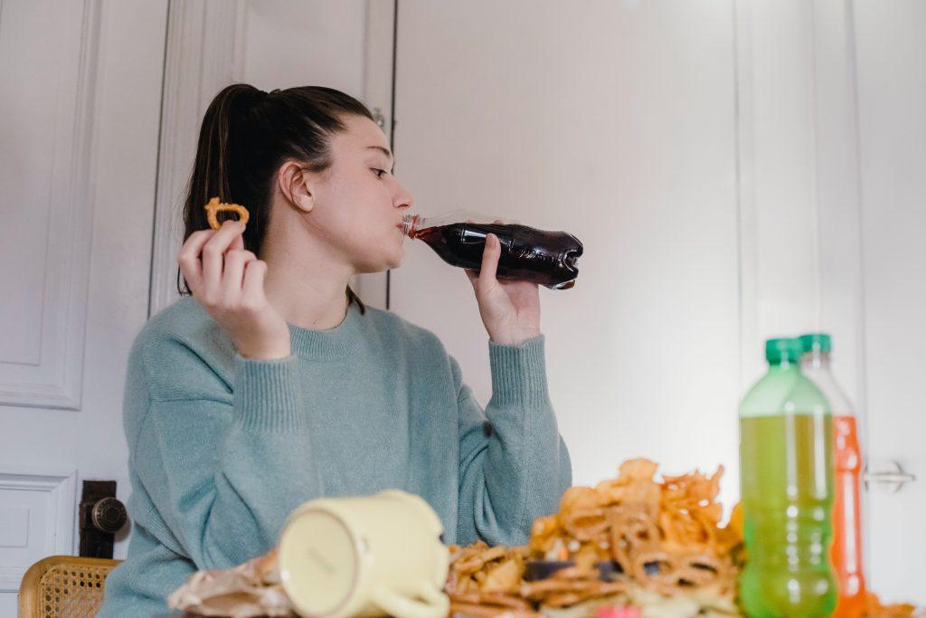 woman drinking soda on a keto cheat day